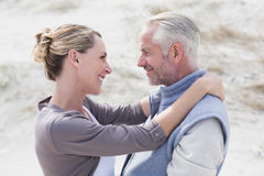Happy hugging couple on the beach looking at each other Royalty Free Stock Photos