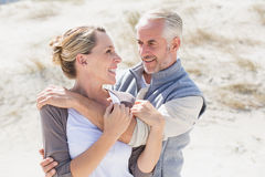 Happy hugging couple on the beach looking at each other Stock Image