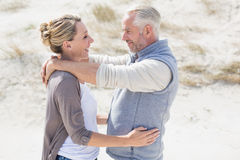Happy hugging couple on the beach looking at each other Stock Photography
