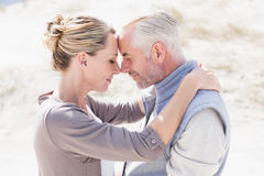 Happy hugging couple on the beach looking at each other Stock Photo