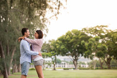 Happy hugging couple. Standing in the park, side view Royalty Free Stock Images