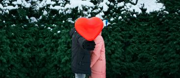 Happy hugging couple in warm winter clothes is standing outdoors with a heart shaped red balloon royalty free stock photos