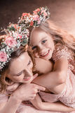 Happy hugging daughter and mother in flowers wreathes. Portrait of happy hugging daughter and mother in flowers wreathes Stock Photography