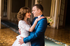 Happy hugging newlyweds in the old baroque castle in Lviv. The bride is holding the wedding bouquet. Stock Photos