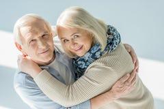 Happy hugging senior couple on white Stock Images
