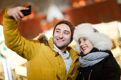 Happy humans photographing themselves outdoors. In winter Stock Photography