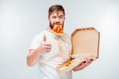 Happy hungry man eating pizza and showing thumbs up gesture Royalty Free Stock Photos