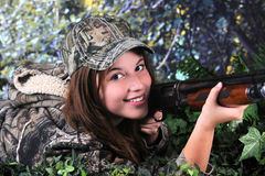Happy Hunter. Close-up image of a pretty young teen hunter looking at the viewer as she lays on the ground ready to hit her prey Royalty Free Stock Photography