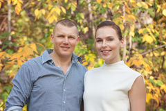 Happy husband embracing wife in autumn park Royalty Free Stock Image