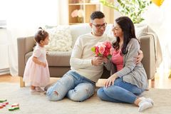 Happy husband giving flowers to his wife at home Royalty Free Stock Photography