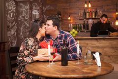 Happy husband giving wife a present in a hipster pub. royalty free stock images