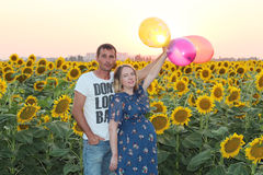 Happy husband and his pregnant wife with balloons in their hands Stock Image