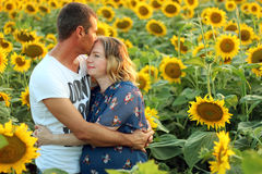 Happy husband and his pregnant wife with sunflowers Royalty Free Stock Photos
