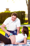 Happy husband with pregnant wife playing in nature Stock Photo