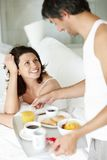 Happy husband serving breakfast for wife to bed Royalty Free Stock Images