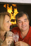 Happy husband and wife. By fireplace with wine Stock Photo