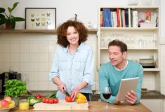 Happy husband and wife together in the kitchen Stock Images