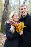 Happy husband and wife with yellow maple leafle laugh. In autumn forest. Shallow depth of field royalty free stock photos