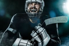 Happy ice hockey player man in the mask and gloves on stadium with stick celebrates victory. Male closeup portrait. Hockey goalie in the mask royalty free stock images