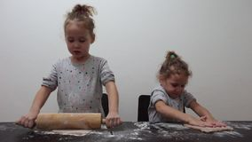 Happy identical twin girls preparing biscuits in the kitchen, casual lifestyle photo in real life interior, christmas cookies. Cute kid in chef dress, Merry stock video