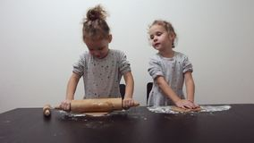 Happy identical twin girls preparing biscuits in the kitchen, casual lifestyle photo in real life interior, christmas cookies. Cute kid in chef dress, Merry stock video footage