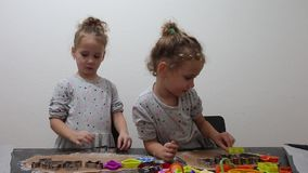 Happy identical twin girls preparing biscuits in the kitchen, casual lifestyle photo in real life interior, christmas cookies. Cute kid in chef dress, Merry stock footage