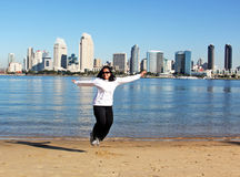 Happy Immigrant. A young Filipino lady jumping in excitement on a beach overlooking the San Diego, California, USA skyline Royalty Free Stock Images