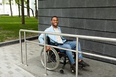 Free Happy Impaired Black Man In Wheelchair Entering Building On Ramp Outdoors, Full Length. Handicapped-accessible City Stock Photography - 220681792