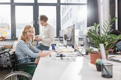 Happy incapacitated person in wheelchair working. At modern office royalty free stock photography