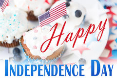 Happy independence day. Celebration, patriotism and holidays concept - close up of cupcakes or muffins decorated with american flags and blueberries on plate stock illustration