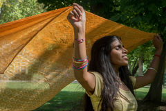 Happy indian beautiful young woman dancing. In the park. Happiness and enjoying the present moment here  and now concept Royalty Free Stock Photography