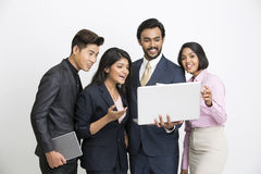Happy Indian business people team happily looking at the laptop. Cheerful Indian business people team happily looking at the laptop on white background Royalty Free Stock Photography