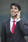 Happy Indian businessman communicating on cell phone Royalty Free Stock Photo