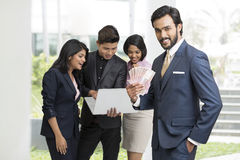 Happy Indian businessman holding rupees with his busy colleagues Royalty Free Stock Images