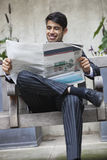Happy Indian businessman reading newspaper while sitting on bench Royalty Free Stock Images