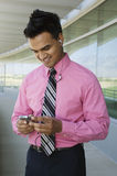 Happy Indian businessman using cell phone Stock Images