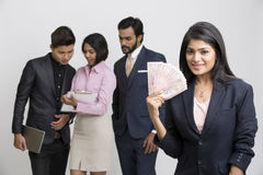 Happy Indian businesswoman holding rupees with her busy colleagues. On white background Royalty Free Stock Image