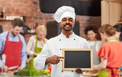 Happy indian chef with chalkboard at cooking class stock photo