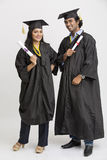Happy Indian college graduates wearing cap and gown holding diploma Royalty Free Stock Photography