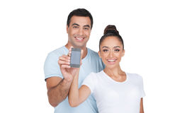Happy Indian couple holding cell phone together. Royalty Free Stock Image