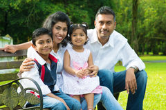 Happy Indian family. At outdoor park. Candid portrait of parents and children having fun at garden park Royalty Free Stock Image