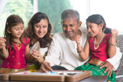 Happy Indian family playing carrom game. Asian Indian family playing carrom game at home. Parents and children indoor lifestyle Royalty Free Stock Images