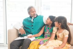 Happy Indian father and daughters bonding. Portrait of Indian family talking at home. Happy Asian father and children indoors lifestyle Royalty Free Stock Image