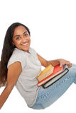 Happy Indian Girl with Books Sitting on the Floor. Close up Portrait of a Happy Indian Girl Holding Books While Sitting on the Floor and Looking at the Camera Royalty Free Stock Photography