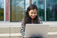 Happy Indian girl with laptop. Happy Indian girl with long dark hair sitting on stairs outdoors, holding laptop, looking at it and smiling. Copy space Stock Image
