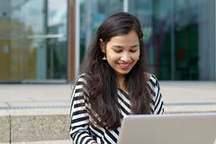 Happy Indian girl with laptop. Happy Indian girl with long dark hair sitting on stairs outdoors, holding laptop, looking at it and smiling. Copy space Royalty Free Stock Image