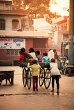 Happy Indian kids playing with wheel cart Stock Photography