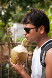 Happy indian man drinking coconut water Stock Photo