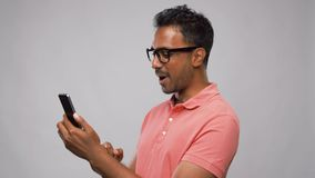 Happy indian man in glasses using smartphone stock footage