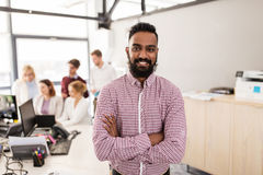 Happy indian man over creative team in office Stock Image
